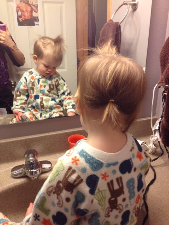 (This picture, which I  posted on Facebook before we told anyone we were pregnant, almost outed me. I meant to show off Peanut's double ponytail hairdo. But I didn't realize Chuck Norris was visible on the bathroom door! I had to make up a BS story about Chucky for the people who noticed. Oops!)