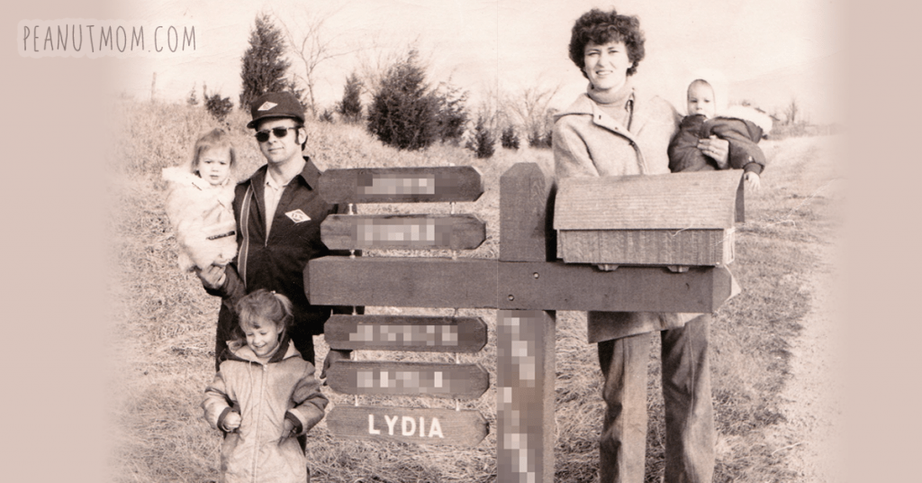 "We lived on a highway when I was a kid, and our mailbox kept getting Louisville Slugger'd, so my dad built one on a huge-ass post that was buried 12 feet into the ground and set with concrete. He added kiddos each time they had another. I'm the little one in my mother's arms, in what I liked to call ""The Happy Time"" before my younger sister came along and knocked me off my 'youngest child' throne. ;-)"